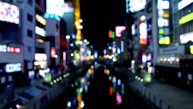 Defokussierten Schuss von Passanten auf der Straße und Nachtbeleuchtung Namba Zone in Osaka, Japan