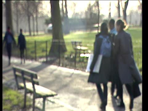 defocused shot of schoolgirls walking along path through park one carries transparent folder full of schoolwork london - adolescence stock videos & royalty-free footage