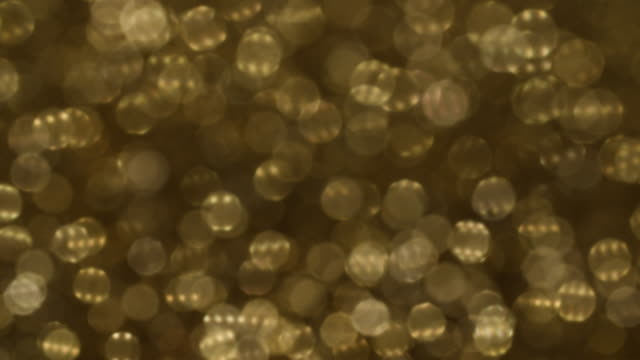 vidéos et rushes de defocused shot on a pile of gold glitter. - or couleur
