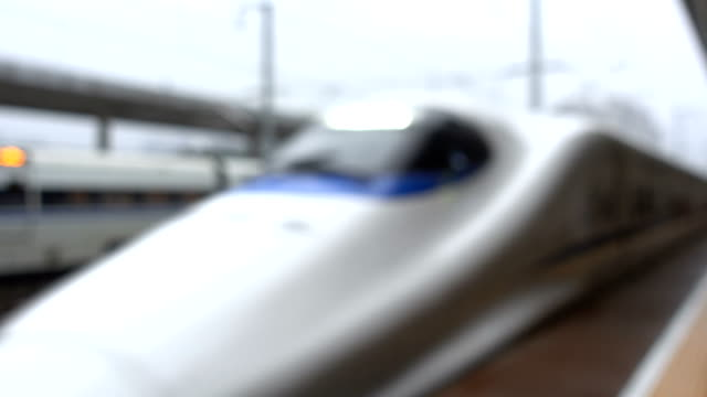 defocused view of high speed train arriving at station - ferrovia video stock e b–roll