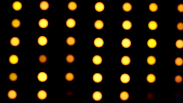 defocused yellow lights blinking on black background - musical theater stock videos and b-roll footage