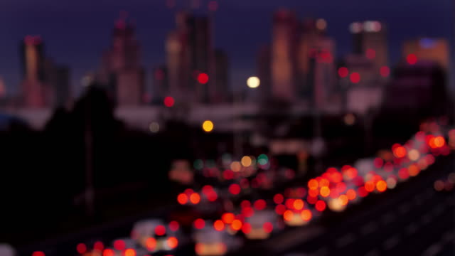 vídeos de stock e filmes b-roll de defocussed city traffic jam. london, canary wharf in the distance. version 2. - luz traseira de carro