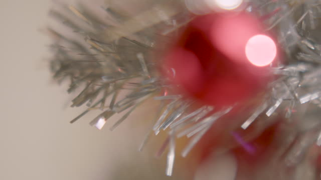 defocussed shot of a red bauble hanging on a silver artificial tree. - tinsel stock videos & royalty-free footage