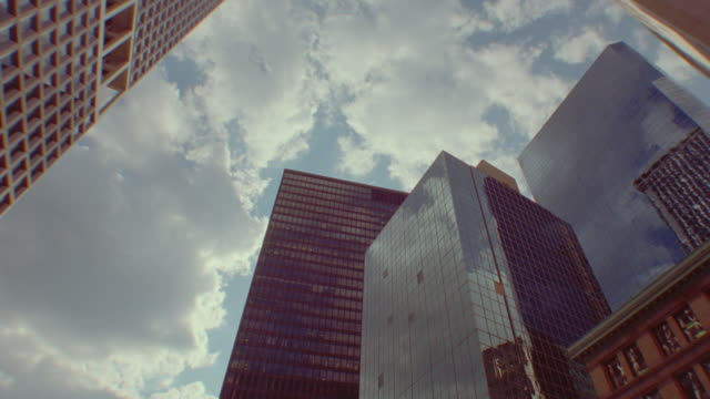 360 degree low angle PAN time lapse clouds in blue sky over skyscrapers / NYC