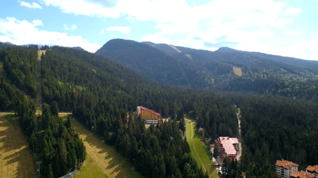 360 degree rotating drone shot panorama of a beautiful but empty ski resort during the summer