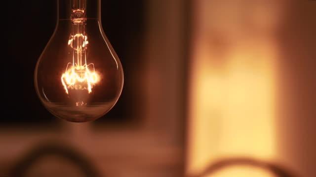 dekorative glühbirne im zimmer wird ein- und ausgeschaltet - 照明器具点の映像素材/bロール