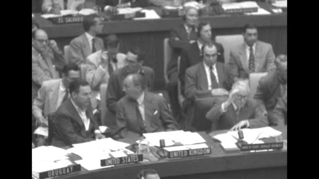 US delegate Henry Cabot Lodge Jr and British delegate Selwyn Lloyd sitting at desks raise their hands to vote yes / Lodge and Lloyd raise hands to...