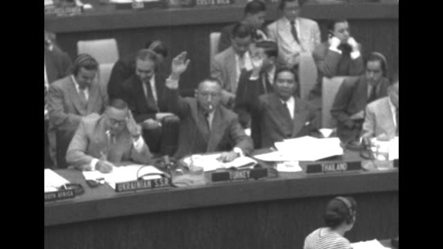 US delegate Henry Cabot Lodge Jr sitting at desk speaking / pan across delegates sitting at desks raising their hands to vote yes / two shots of...