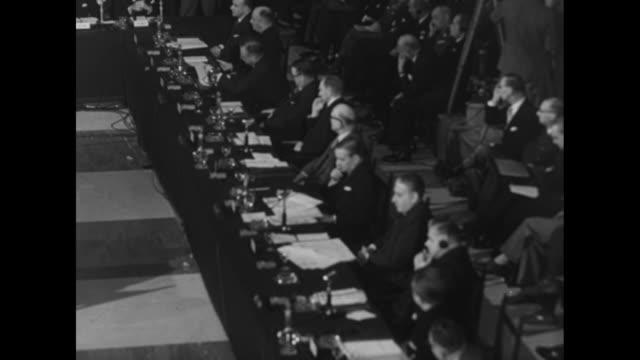 delegates at seats at tables inside the foro italico as meeting of north atlantic council continues / tilt-down delegate, possibly belgian foreign... - ordförande bildbanksvideor och videomaterial från bakom kulisserna
