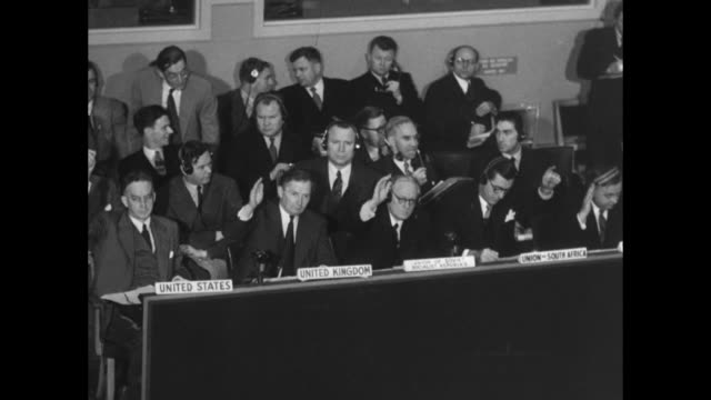 Delegates from United States United Kingdom Soviet Union and Union of South Africa raise hands in unison Soviet delegate is Andrey Vyshinsky / pan...