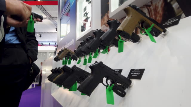 delegates look at some of the hand guns displayed on the beretta defense technologies stand on day one of the dsei arms fair at excel on september 10... - camouflage stock videos & royalty-free footage