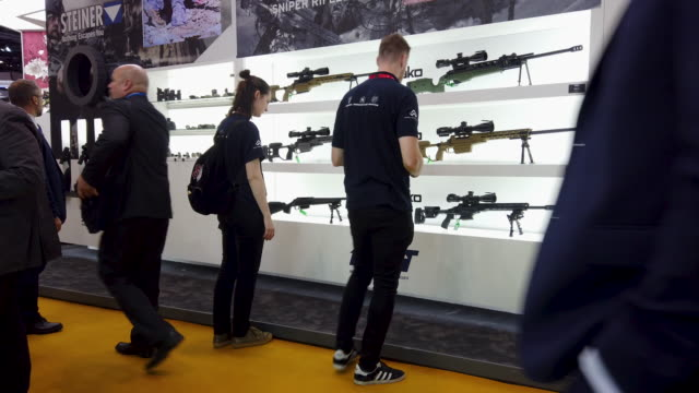 delegates look at some of the sniper rifles displayed on the beretta defense technologies stand on day one of the dsei arms fair at excel on... - weaponry stock videos & royalty-free footage