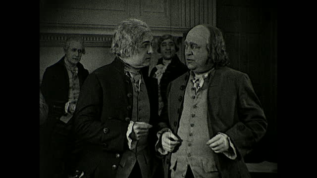 """vídeos de stock e filmes b-roll de delegates standing together discussing the signing of the declaration of independence as john hancock is signing: """"if it comes to hanging, charles... - século xviii"""