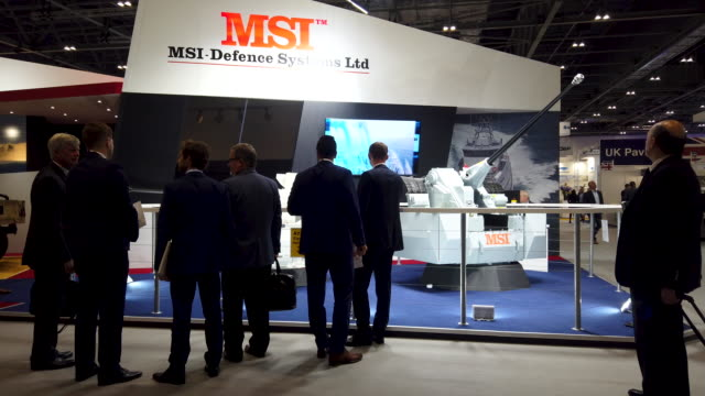 delegates stop to look at an automated weapons system on the msi defence systems ltd stand on day one of the dsei arms fair at excel on september 10,... - exhibition stock videos & royalty-free footage