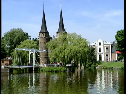 delft general views; netherlands: delft: ext dutch woman pumping air into bicycle wheel / picturesque view of canal waterway with spires of eastern... - general view stock videos & royalty-free footage