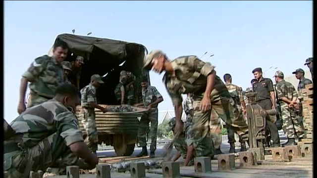 stockvideo's en b-roll-footage met army repairs collapsed bridge india delhi ext indian soldiers unloading bridge parts from back of truck outside nehru stadium 'work in progress' sign... - indiase leger