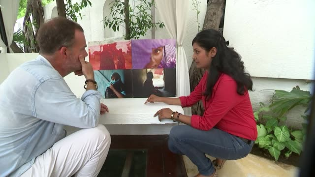 Indian women still living in fear of sexual violence INT Smita Sharma looking at display of her photographs with reporter/ Smita Sharma interview SOT