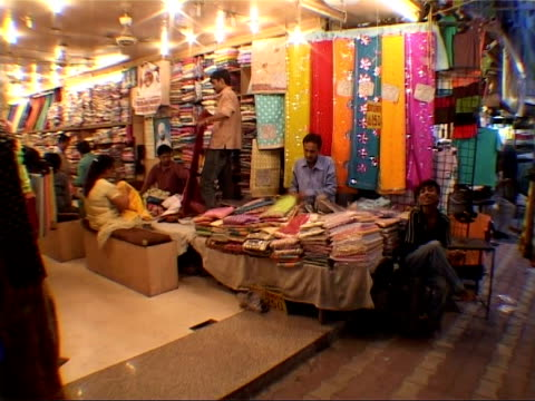 General Views Man working at sewing machine in market using foot pedals to sew / shop selling cloth and material for saris / customers looking at...