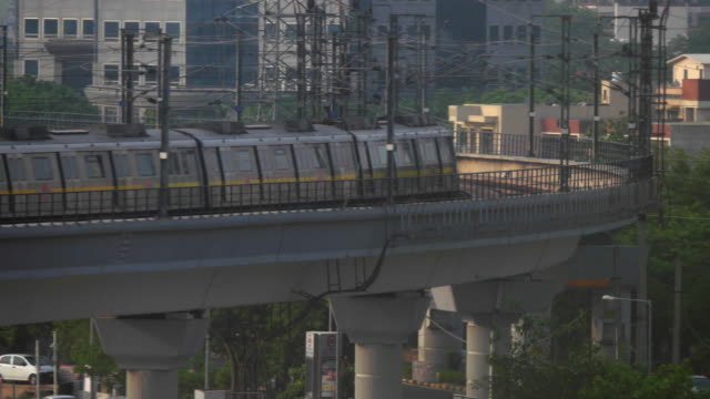 delhi metro train on the yellow line passing across a curved elevated section after the huda city centre metro station in gurgaon, with commercial buildings in the background - delhi stock videos & royalty-free footage