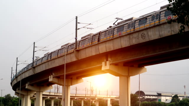 delhi metro train passing over bridge during sunset time - rail transportation stock videos & royalty-free footage