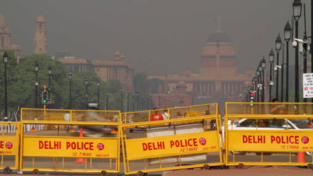 Delhi police security barricades on Rajpath road as viewed from India Gate and looking towards the Presidential Palace, New Delhi, India