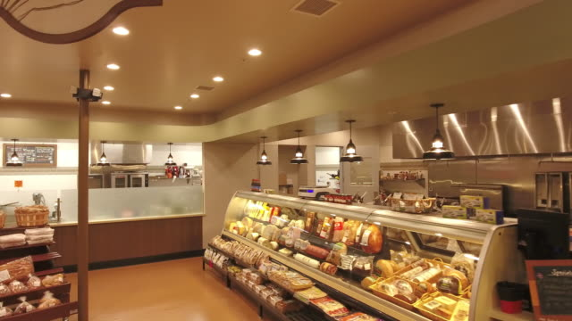 ds deli section in grocery store with display cases showing hams and cheeses - 肉点の映像素材/bロール