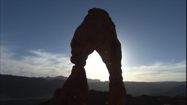 Delicate Arch rises in silhouette against a blue sky in Arches National Park, Utah.