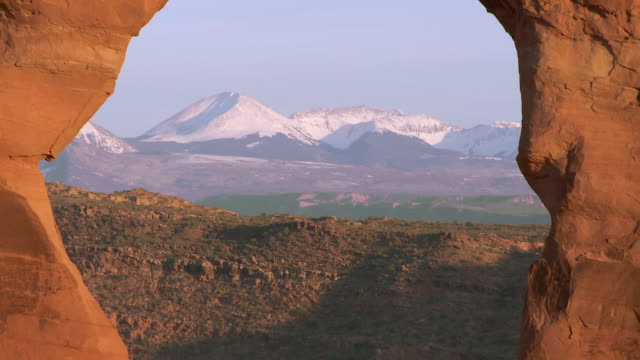 Delicate Arch -- zoom out from La Sal mountain peaks in distance to reveal the entire arch framing the mountains inside
