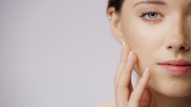 vídeos de stock e filmes b-roll de delicate, shy woman face skin care. touching her smooth skin - acariciar