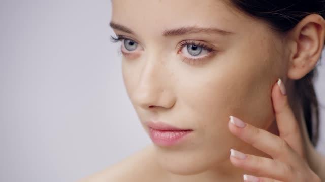 vidéos et rushes de soins délicats et timides de la peau de visage de femme. toucher sa peau lisse - cheveux bruns