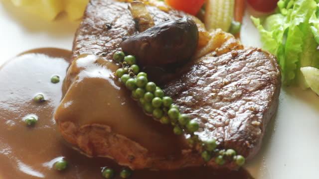 vídeos de stock, filmes e b-roll de bife de carne delicioso com molho e os peppercorns verdes frescos na placa. - bbq sauce