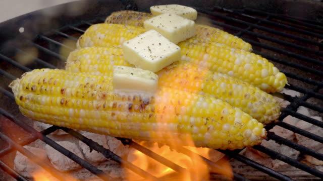 vídeos y material grabado en eventos de stock de delicious carbonizado mantecoso choclos elotes en una parrilla ardiente - maíz alimento