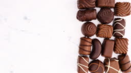 Delicious chocolates various shapes on marble background - Stop motion