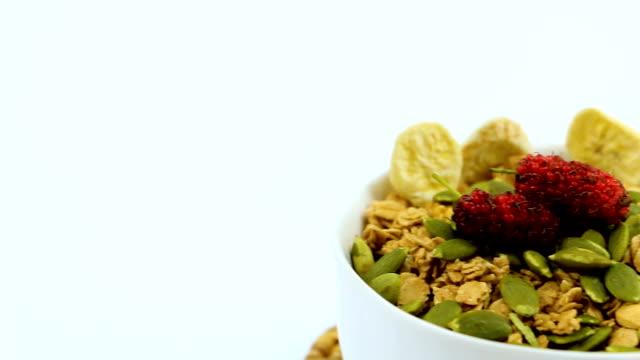 stockvideo's en b-roll-footage met heerlijke nutriënten, licht scherpe vlokken van rijst en tarwe in de kom op de houten tafel, met bessen vruchten, low fat meer eiwit en folaat. - volkoren