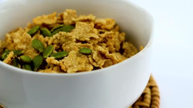 stockvideo's en b-roll-footage met heerlijke nutriënten, licht scherpe vlokken van rijst en tarwe in de kom op de houten tafel, met bessen vruchten, low fat meer eiwit en folaat. - volkorentarwe