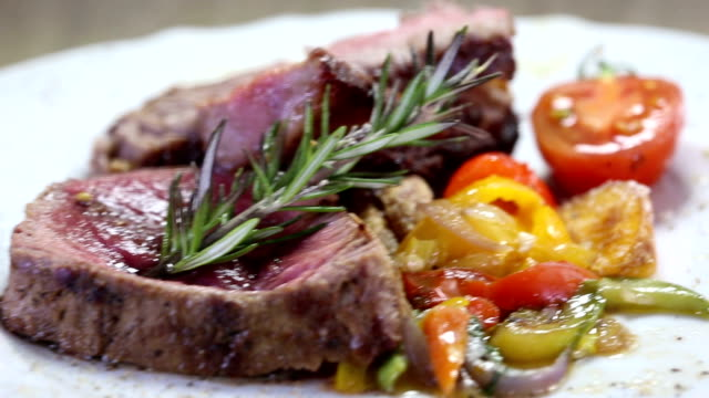 delicious steak with vegetables - dolly video - filleted stock videos & royalty-free footage