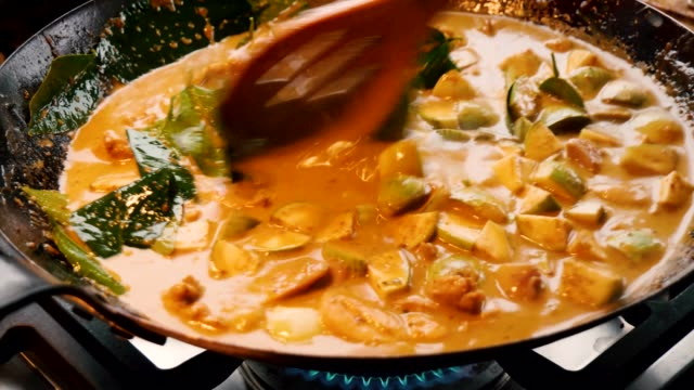 stockvideo's en b-roll-footage met delicious thai food meal of vegetables and red curry are cooking and stirred in black wok with slatted wooden spoon, static close up - pan keukengereedschap