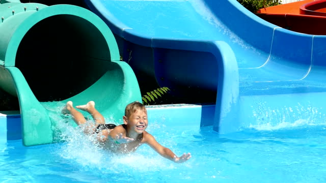 delight the child on the water slides in the water park (slow motion) - water slide stock videos & royalty-free footage