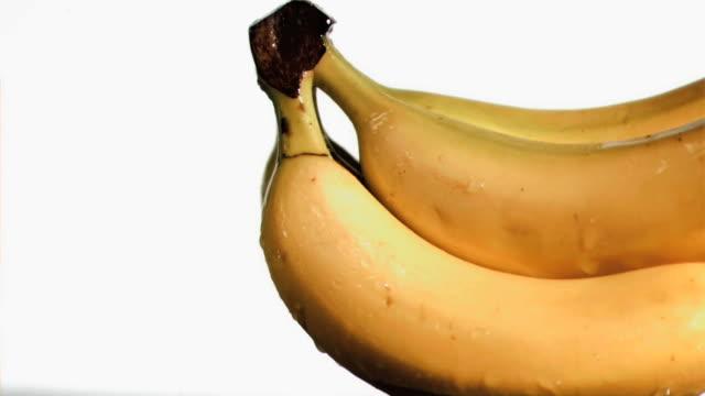delightful bananas in super slow motion receiving water - slip banana stock videos & royalty-free footage