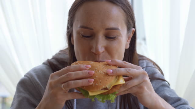 delighthed woman tasting a big hamburger at home - hungry stock videos and b-roll footage