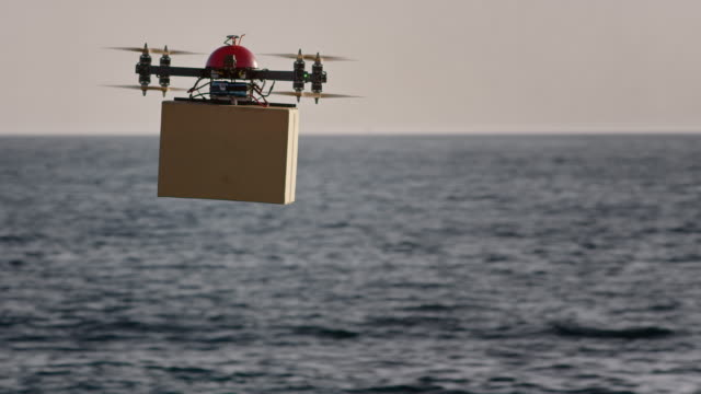 SLO MO UAV delivering package above sea surface in sunshine