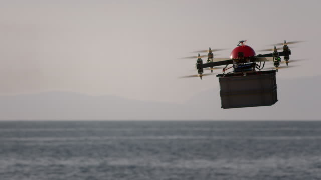 SLO MO UAV delivering plastic box across sea at sunset