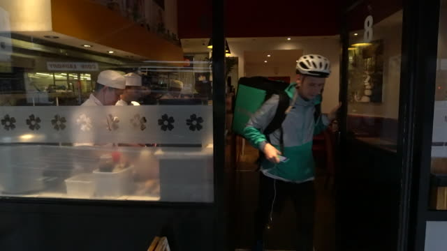 vídeos de stock, filmes e b-roll de a deliveroo courier leaves a restaurant with a takeaway delivery absa627d - entregador