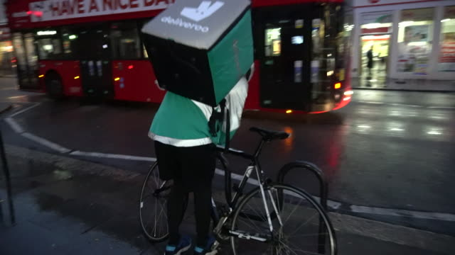 deliveroo courier leaves a restaurant with a takeaway delivery. absa627d - fast food stock videos & royalty-free footage