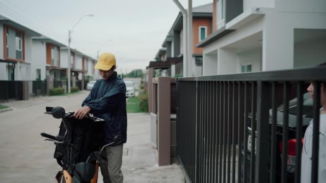 宅配アジア人が自宅でお客様に食べ物を届ける - home economics点の映像素材/bロール