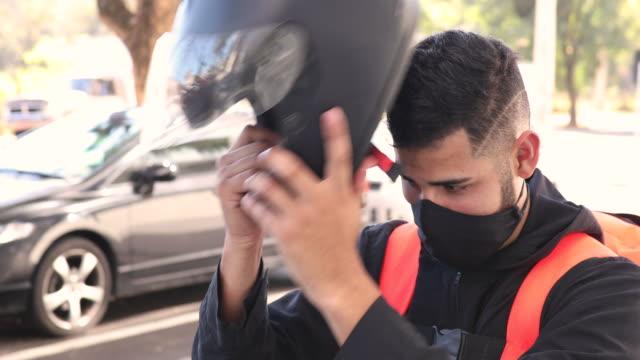 vídeos de stock, filmes e b-roll de delivery biker taking crash helmet off - motoboy - motocicleta