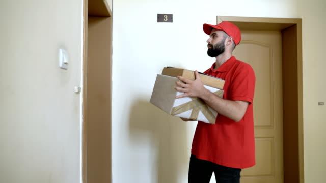 austräger ankunft an die adresse des empfängers und klingelt an der tür - abwarten stock-videos und b-roll-filmmaterial
