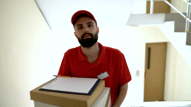 delivery boy in red uniform looking at camera - man made object stock videos & royalty-free footage