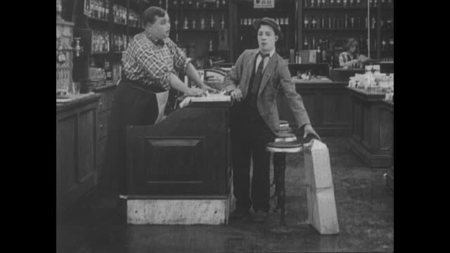 vídeos y material grabado en eventos de stock de 1917 a delivery boy (buster keaton) who balances a box on his head crashes his bike in front of a drugstore - caja