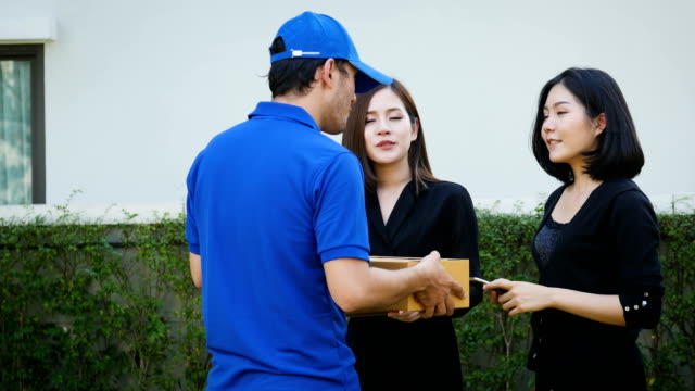 Delivery concept, Woman giving credit card to the delivery man to pay for the order after receiving parcel from courier at home